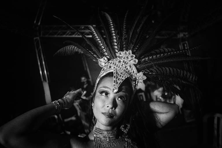 Cecília Lero, 35, se prepara para se apresentar como passista da ala-show; ela, que veio das Filipinas, desfila na Gaviões da Fiel há seis anos; a foto preto e branco mostra uma mulher de feições orientais, enquadrada na altura dos ombros, colocando um adereço de cabeça;