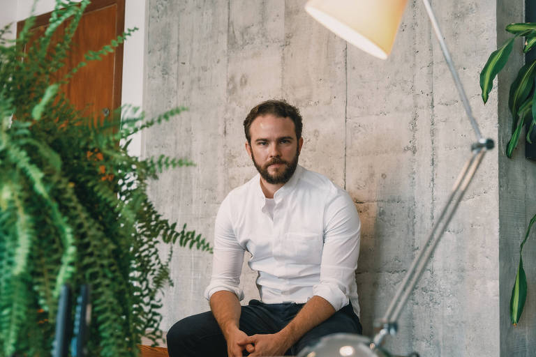 Homem de camisa branca sentado ao lado de luminária e planta