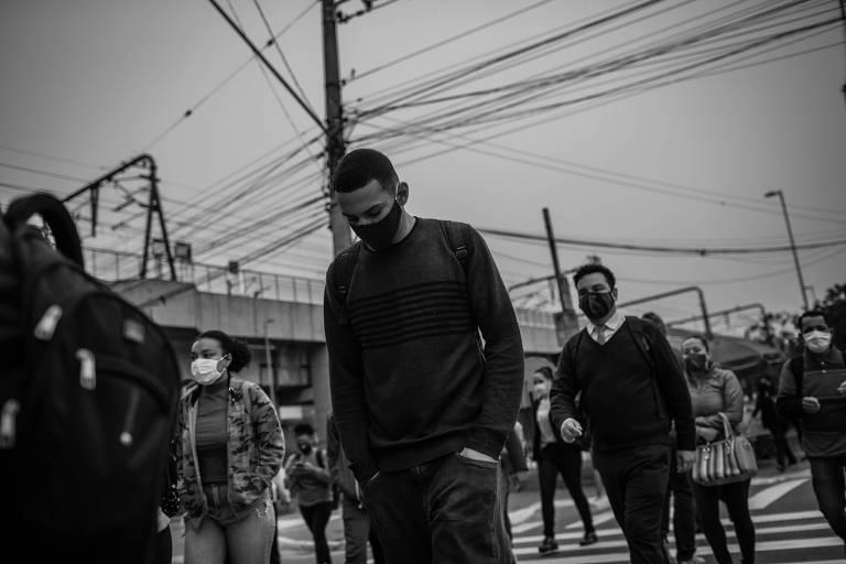 Várias pessoas atravessando a rua, com máscaras de proteção contra o coronavírus.