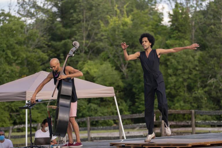 Homem dança e outro toca instrumento ao lado