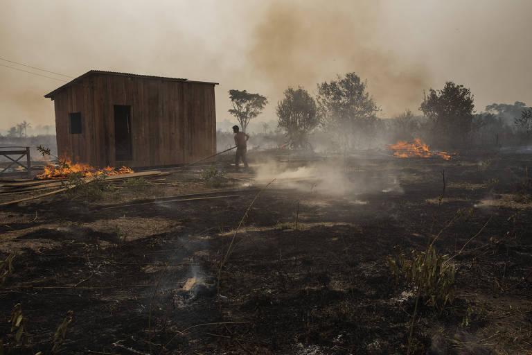 Na foto, há um pasto com um barraco em chamas, e o ar carregado de fumaça acobreada