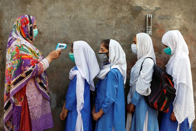 Mulher aponta equipamento na testa de estudantes, que estão em fila e usam máscara de proteção