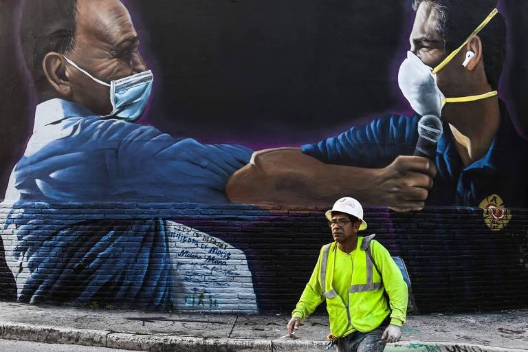 Trabalhador do setor de construção civil caminha em frente a mural que mostra o prefeito de Miami, Francis Suárez, à dir., no bairro de Wynwood