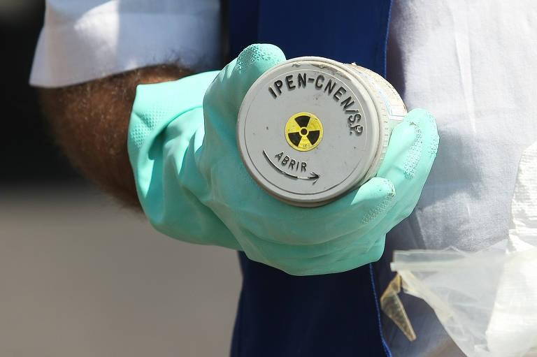 Cápsula cinza com etiqueta escrita 'Ipen', indicando que o material é radioativo