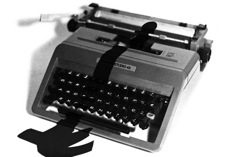 sombra de homem sobre máquina de escrever