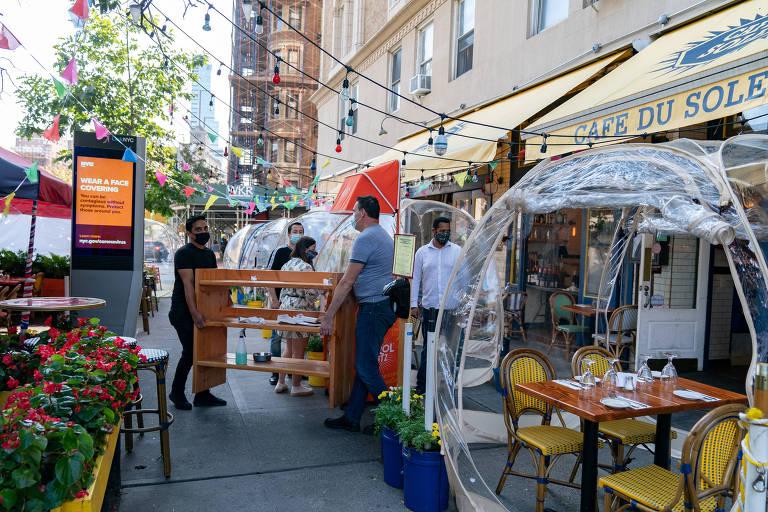 Pessoas montando bolhas de plástico em mesas em calçada