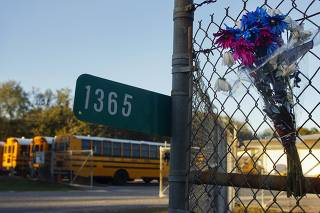 Flowers, in honor of murdered school bus driver Charles Poland, are attached to a fence at the entrance to the Dale County Bus Barn on Highway 27 outside Ozark