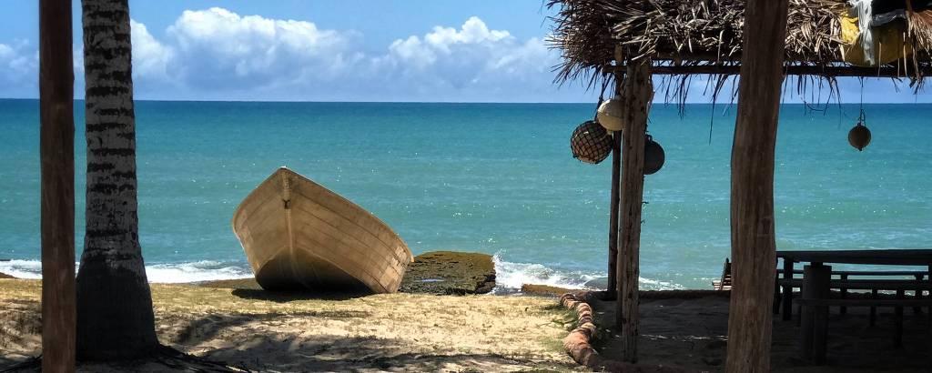 Barco parado na areia, em praia vazia, com construção de madeira