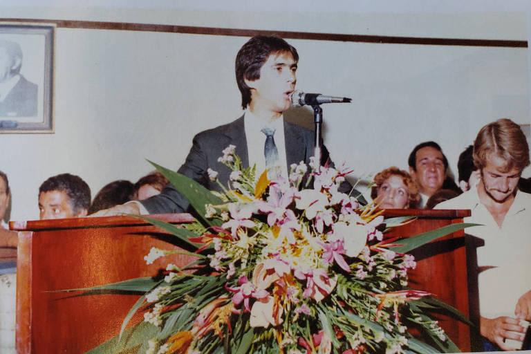 Homem de terno e gravata discursa em púlpito, com arranjo de flores na frente