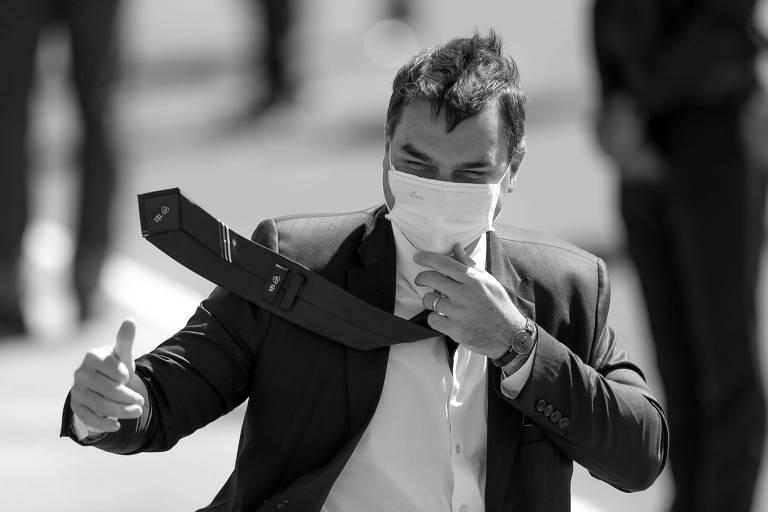 Flávio Bolsonaro com máscara de proteção, terno e gravata, cumprimentando seguidores em Brasília.