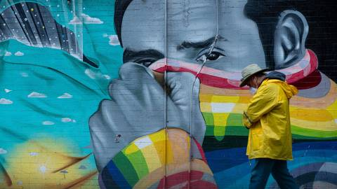 TOPSHOT - A man wearing a mask passes a mural on April 13, 2020 in New York City. - New York's governor declared April 13, 2020 that the