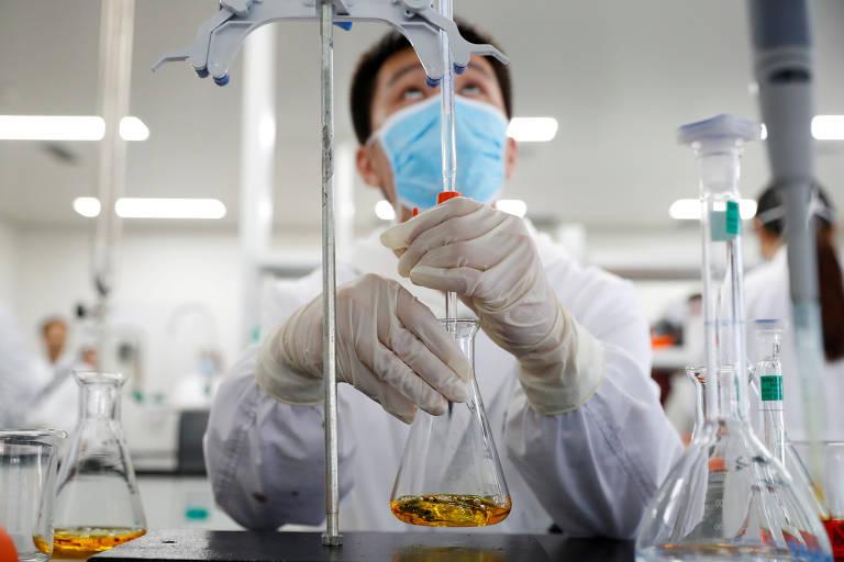 Cientista com máscara azul e avental branco segura frasco de vidro com líquido de cor dourada e pipeta em laboratório