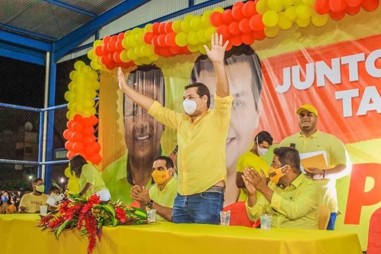 Homem de meia idade com camisa amarela ergue os braços em uma pequena tribuna com flores e balões amarelos e laranjas