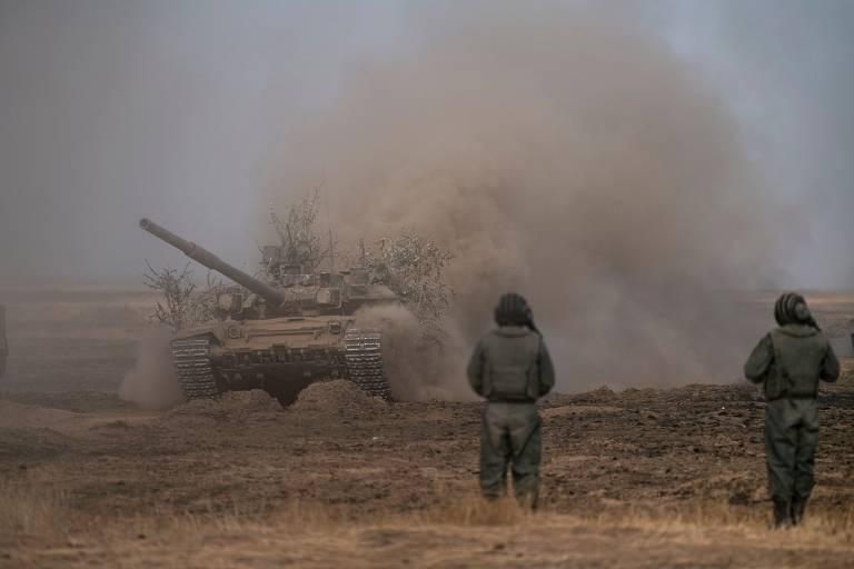 Soldados russos observam um tanque T-72-B3 em ação na região de Volgogrado