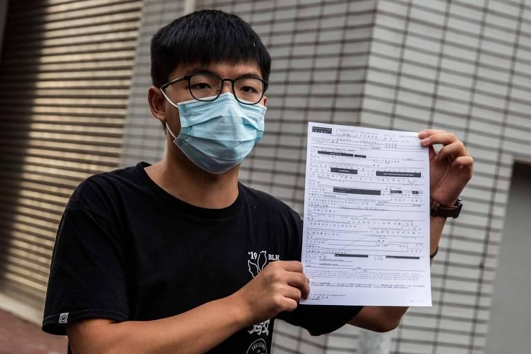 Após deixar delegacia em Hong Kong, o ativista pró-democracia Joshua Wong segura documento que atesta pagamento de fiança