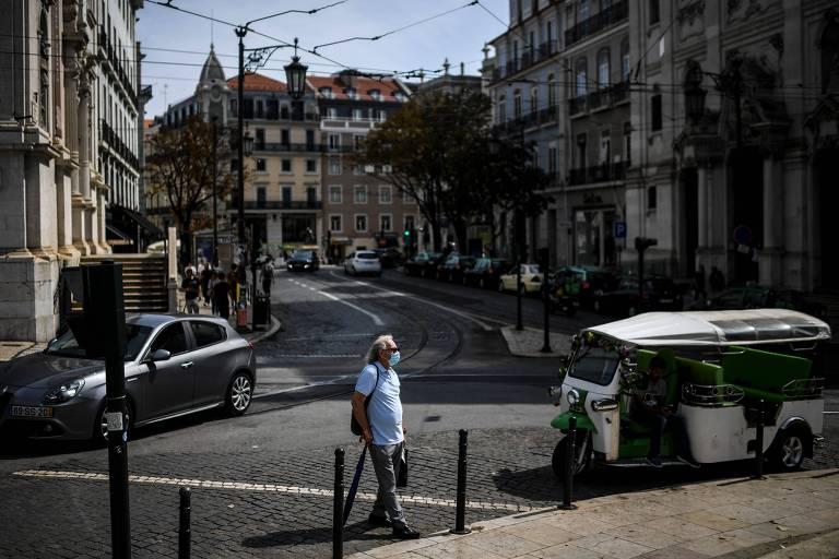Homem com máscara atravessa rua vazia em Lisboa