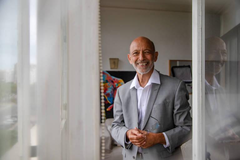 homem branco careca de terno cinza e camisa social posa para foto em uma sala com muitos quadros pendurados na parede