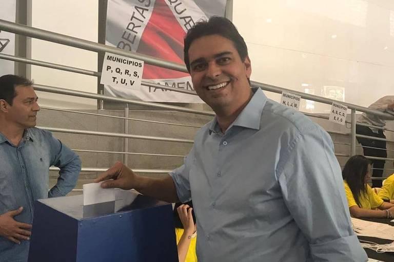Homem de camisa azul clara deposita cédula de papel em urna de papelão
