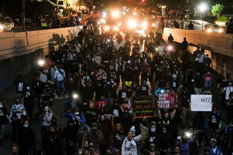 Multidão com cartazes em rua à noite