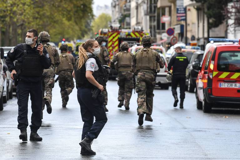 Policiais no meio da rua; ao fundo há uma ambulância