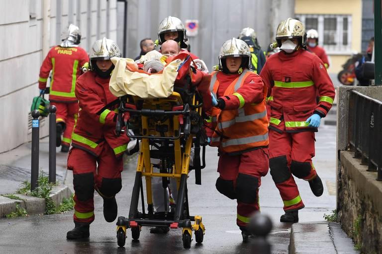 Equipes de resgate tiram vítima de atentado em Paris do local do crime