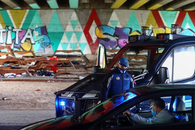 Policial checa documentos em bloqueio no bairro de Villaverde, parte das restrições por zona realizadas em Madri