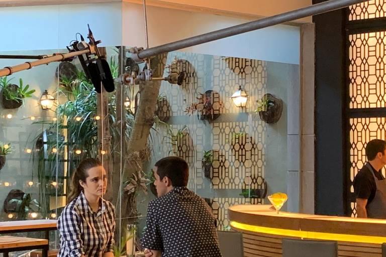 """Os atores Juliana Paiva e Felipe Simas aparecem sentados em uma mesa de restaurante, com uma barra de acrílico dividindo os dois, na novela """"Salve-se Quem Puder"""""""