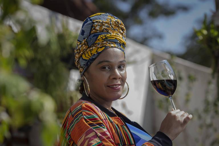 Mulher negra com turbante, olhando para a câmera e segurando uma taça de vinho tinto