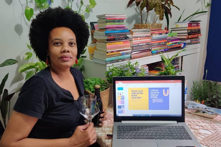 mulher negra com blusa preta ao lado de notebook