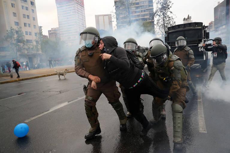 Policiais detêm manifestante durante protesto contra o governo em Santiago, no Chile