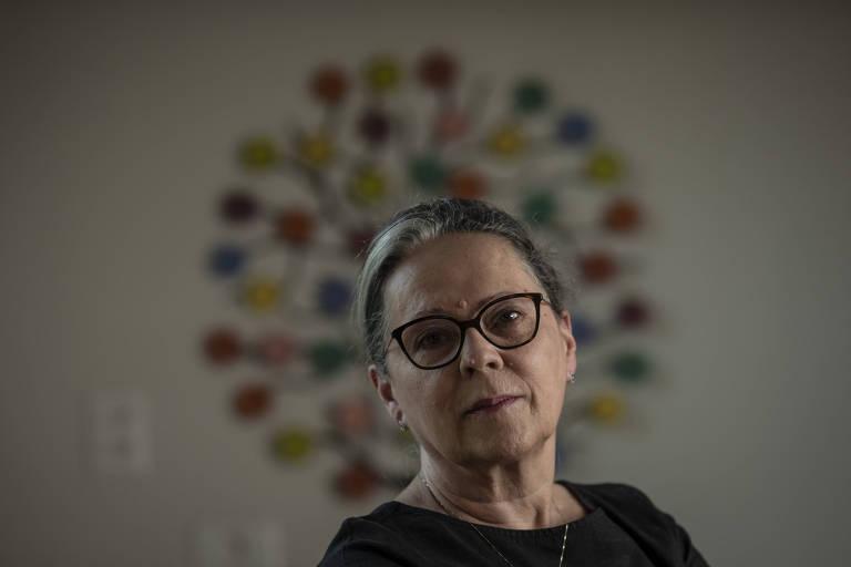 Retrato de Maria Cristina, que olha pra a câmera. Ao fundo, desfocado, uma obra de arte que lembra uma flor