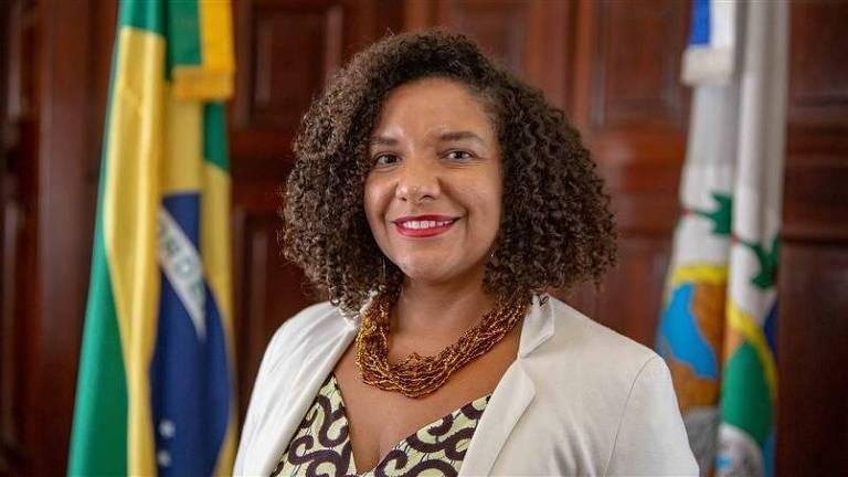 Mulher de casaco branco e colar sorri, com a bandeira do Brasil ao fundo