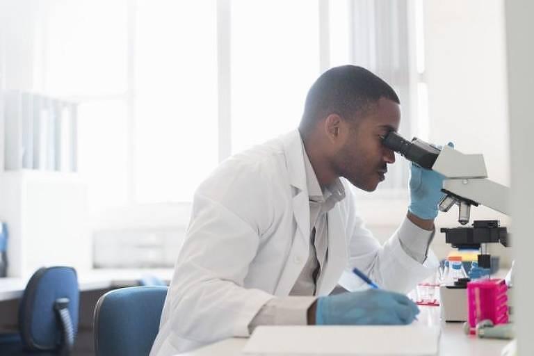 homem negro veste jaleco branco e luvas azuis. ele está  sentado em um laboratório e olha através de um microscópio