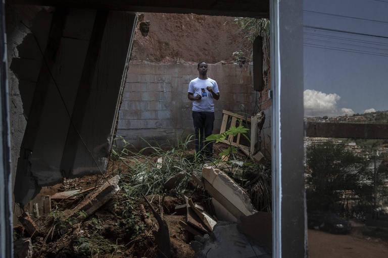 Um homem ao fundo dos escombros de uma casa segura o retrato de um garoto. Do lado de fora, a vista da rua de terra e casas empilhadas nas encostas