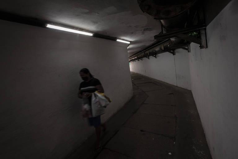 Uma mulher dentro de um túnel, escuro apesar das lâmpadas de led e paredes brancas