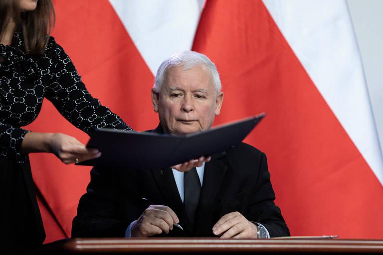 Homem de terno preto em frente a duas bandeiras vermelhas e brancas recebe documento para assinar