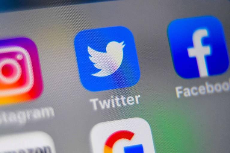 Símbolos das redes sociais Instagram, Twitter e Facebook em tela de smartphone