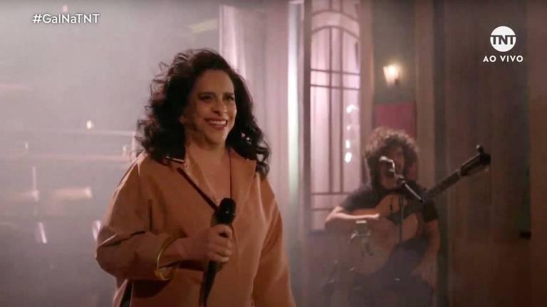 cantora à frente de guitarrista em palco esfumaçado