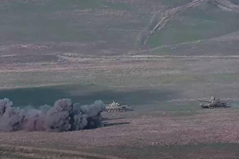 Tanques de guerra em campo, ao lado de pilar de fumaça