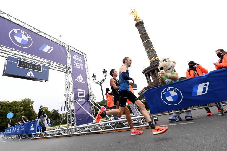 Atletas correm com monumento ao fundo