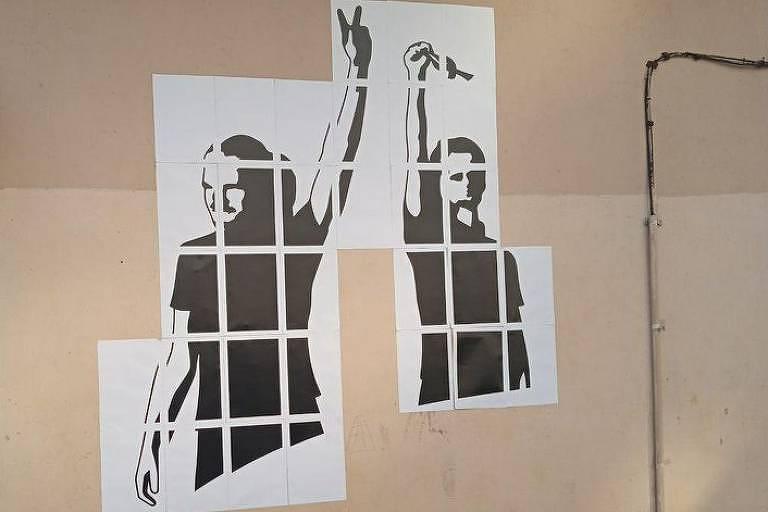 Graffiti mostra dois jovens com os braços levantados, um faz o sinal de V e outros mostra o punho fechado