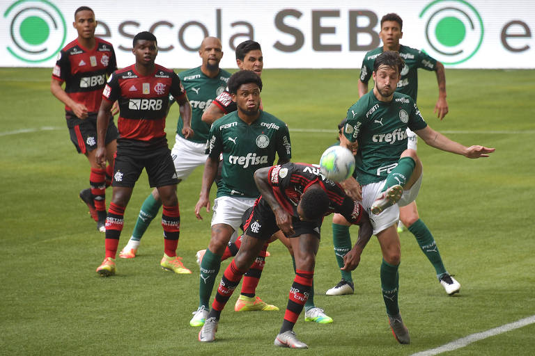 Gerson, do Flamengo, tenta cabecear a bola em disputa com Vina, do Palmeiras