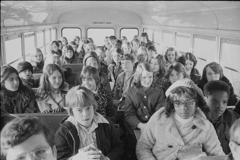 Crianças negras e brancas em um ônibus escolar, viajando dos subúrbios até uma escola no centro da cidade de Charlotte, na Carolina do Norte (EUA), em 1973