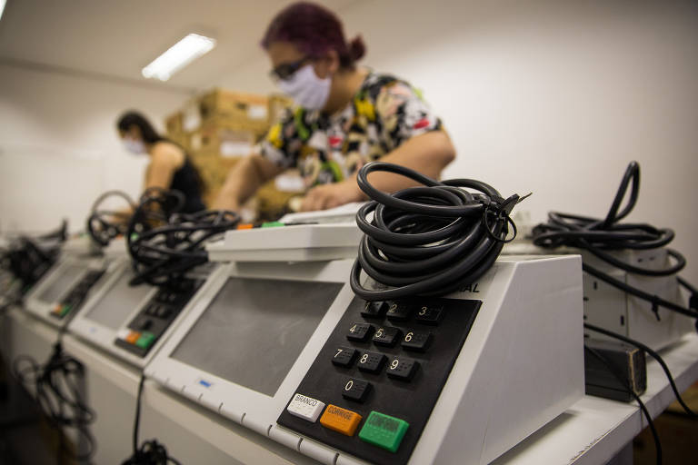 Com a pandemia ainda em curso e o número de mortes e casos confirmados aumentando, as eleições brasileiras foram adiadas para novembro de 2020. Na foto, servidores da Justiça Eleitoral ajustam as urnas e adicionam equipamento de proteção na 1ª Zona Eleitoral, da Bela Vista