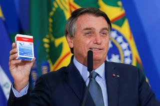 Brazil's President Jair Bolsonaro holds a box of chloroquine during an inauguration ceremony of the new Health Minister