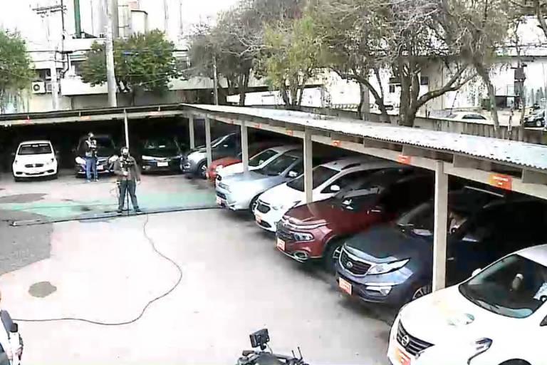 Estacionamento com carros e equipe de tv no meio