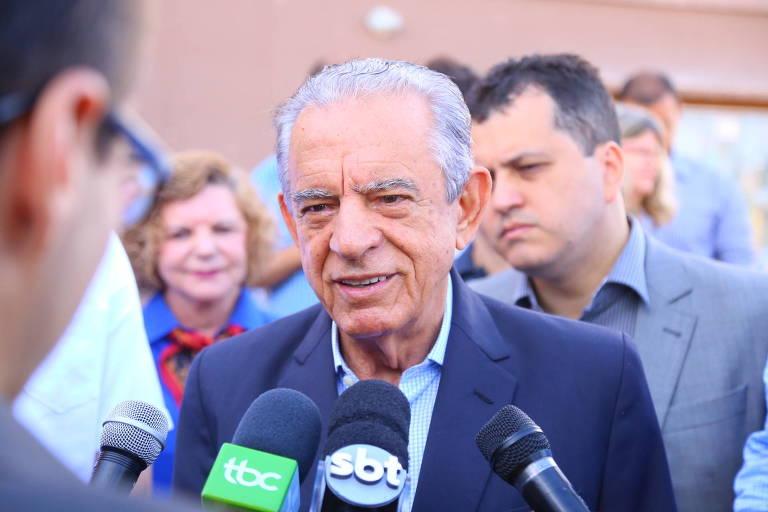 O prefeito Iris Rezende, de blaser e camisa listrada, com microfones em sua frente e pessoas ao fundo.