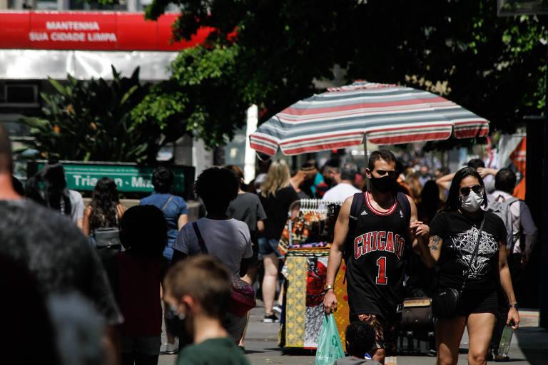 Pedestres enfrentam forte calor na avenida Paulista, região central de São Paulo, durante o domingo