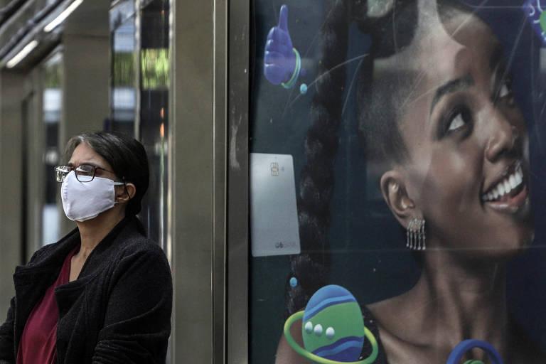 Mulher usa máscara enquanto espera pelo seu ônibus em São Paulo