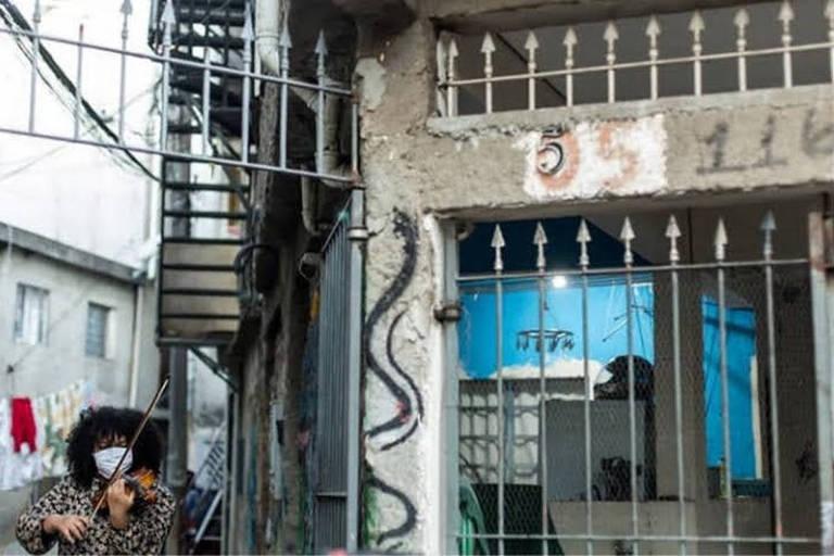 Moça negra de máscara toca viola ao lado de casa em favela de São Paulo